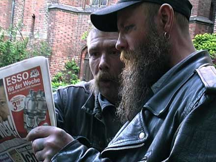 two homeless men reading newspaper