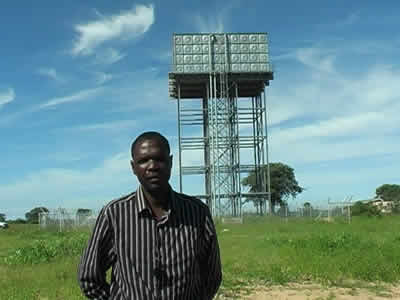 Man in front of water tower